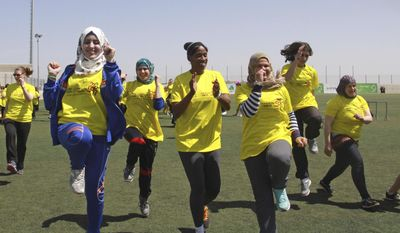 American track and field great Jackie Joyner-Kersee, center, jogs with Palestinian women in the West Bank city of Ramallah, Thursday, April 17, 2014. The three-time Olympic gold medalist visited the West Bank to encourage Palestinian women to be physically active. (AP Photo/Nasser Shiyoukhi)