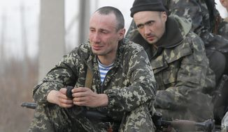 Soldiers of the Ukrainian Army react as they sit a top combat vehicles as they are blocked by people on their way to the town of Kramatorsk, Ukraine, Wednesday, April 16, 2014. The central government has so far been unable to rein in the insurgents, who it says are being stirred up by paid operatives from Russia and have seized numerous government facilities in at least nine eastern cities to press their demands for broader autonomy and closer ties with Russia. (AP Photo/Efrem Lukatsky)