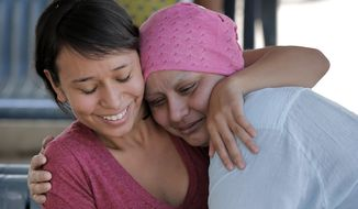 Ruth Alvarez, right, is hugged by her daughter Indira Alvarado, shortly after Alvarez was released from jail, Thursday, April 17, 2014 in Phoenix. Alvarez, who was arrested for using fake identification to get work, reached a deal with the Maricopa County Attorney's Office to be released from jail to undergo a planned mastectomy. Alvarez was arrested April 1st, just a few weeks shy of a scheduled mastectomy she planned to undergo on April 23rd. (AP Photo/Matt York)