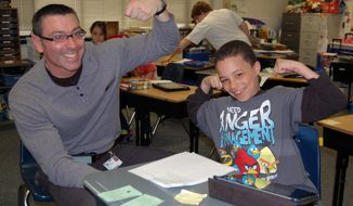 ADVANCE FOR RELEASE MONDAY, APRIL 21, 2014, AT 12:01 A.M. CDT, AND THEREAFTER - In this undated photo, Burdge Elementary School Principal Joe Vrydaghs flexes his muscles along with fourth grader Jaelon Ramage, in Beloit, Wis. Vrydaghs participates in bodybuilding competitions and tries to inspire his students to stay fit. Jaelon said he lifts 5-pound weights, and hopes to become big and strong like his principal. (AP Photo/The Beloit Daily News, Hillary Gavan)