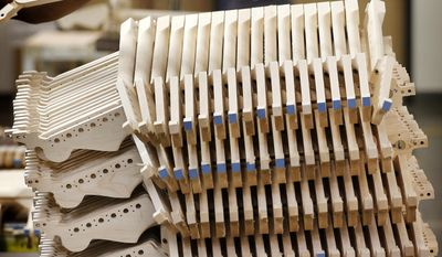 Fender Stratocaster electric guitar necks are prepared for assembly at the Fender factory in Corona, Calif. Leo Fender developed the instrument in a small workshop in Fullerton, Calif. six decades ago. (AP Photo/Matt York)