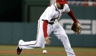 Washington Nationals third baseman Anthony Rendon can't field a hit by St. Louis Cardinals' Allen Craig during the eighth inning of a baseball game at Nationals Park on Thursday, April 17, 2014, in Washington. The Cardinals won 8-0. (AP Photo/Alex Brandon)