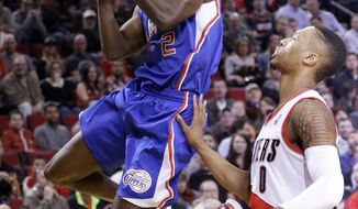Los Angeles Clippers guard Darren Collison, left, drives to the basket past Portland Trail Blazers guard Damian Lillard during the first half of an NBA basketball game in Portland, Ore., Wednesday, April 16, 2014. (AP Photo/Don Ryan)