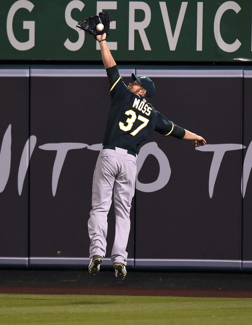 Oakland Athletics first baseman Brandon Moss makes a catch on a fly ball hit by Los Angeles Angels' Howie Kendrick during the seventh inning of a baseball game, Wednesday, April 16, 2014, in Anaheim, Calif. (AP Photo/Mark J. Terrill)
