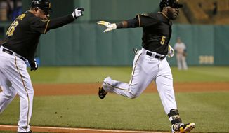 Pittsburgh Pirates' Josh Harrison (5) rounds third to greetings from coach Nick Leyva (16) after hitting a two-run home run off Milwaukee Brewers relief pitcher Rob Wooten during the seventh inning of a baseball game in Pittsburgh, Thursday, April 17, 2014. (AP Photo/Gene J. Puskar)