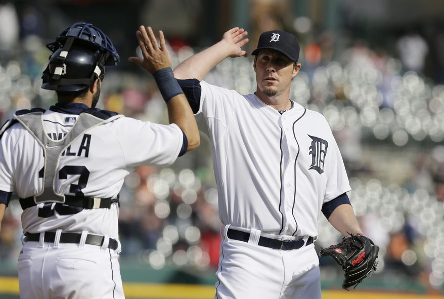 Detroit Tigers relief pitcher Joe Nathan high-fives catcher Alex Avila after the Tigers' 7-5 win over the Cleveland Indians in a baseball game in Detroit, Thursday, April 17, 2014. (AP Photo/Carlos Osorio)