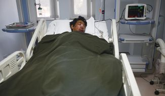 A Nepalese Sherpa Dawa Tashi, who was injured during an avalanche, gets treatment at a hospital in Katmandu, Nepal, Friday, April 18, 2014. An avalanche swept down a climbing route on Mount Everest early Friday, killing at least 12 Nepalese guides and leaving three missing in the deadliest disaster on the world's highest peak. (AP Photo/Niranjan Shrestha)