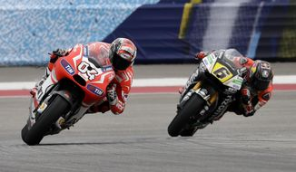 Andrea Dovizioso of Italy leads Stefan Bradl (6) of Germany out of Turn 5 during the Grand Prix of the Americas MotoGP motorcycle race, Sunday, April 13, 2014, in Austin, Texas. Dovizioso finished third in the race.  (AP Photo/Tony Gutierrez)