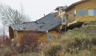 A house breaks apart as a slow-moving landslide in Jackson, Wyo. advances downhill on Friday, April 18. 2014.  The slide has cut off access to a 60-person neighborhood and has threatened town utilities, including a water line. (AP Photo/Jackson Hole News and Guide, Angus M. Thuermer Jr)