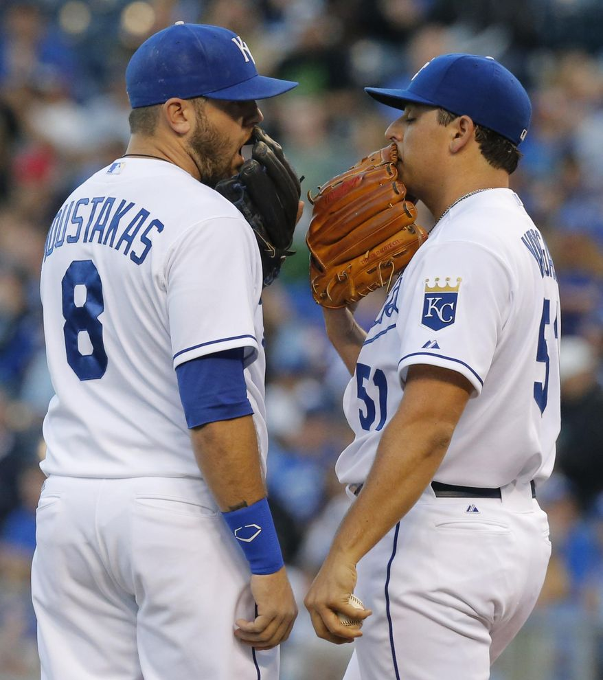 Kansas City Royals third baseman Mike Moustakas (8) talks with starting pitcher Jason Vargas, right, between batters during the first inning of a baseball game against the Minnesota Twins at Kauffman Stadium in Kansas City, Mo., Friday, April 18, 2014. (AP Photo/Orlin Wagner)