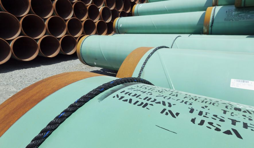 This May 24, 2012, file photo shows some of about 500 miles worth of coated steel pipe manufactured by Welspun Pipes, Inc., originally for the Keystone oil pipeline, stored in Little Rock, Ark. (AP Photo/Danny Johnston, File)