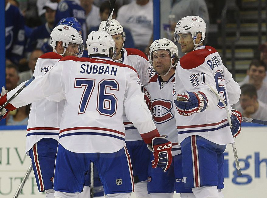 Montreal Canadiens center David Desharnais (51) celebrates with teammates, including P.K. Subban (76) and Max Pacioretty (67), after scoring against the Tampa Bay Lightning during the second period of Game 2 of a first-round NHL hockey playoff series on Friday, April 18, 2014, in Tampa, Fla. (AP Photo/Chris O'Meara)