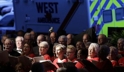 A West emergency vehicle sits parked behind the Baylor Singing Seniors, a choir, as they perform at the beginning of a memorial service, Thursday, April 17, 2014, in West, Texas, honoring the persons who were killed in a fertilizer plant explosion one year ago. (AP Photo/Tony Gutierrez)