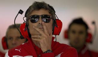 Ferrari's new team principal Marco Mattiacci, center, watches the monitor during the practice session ahead of Sunday's Chinese Formula One Grand Prix at Shanghai International Circuit in Shanghai, China Friday, April 18, 2014.  (AP Photo/Andy Wong)