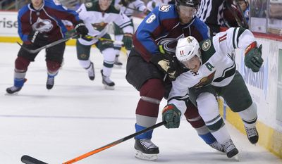 Minnesota Wild left wing Zach Parise (11) ducks under Colorado Avalanche defenseman Jan Hejda (8), from the Czech Republic, during the first period in Game 1 of an NHL hockey first-round playoff series on Thursday, April 17, 2014, in Denver. (AP Photo/Jack Dempsey)
