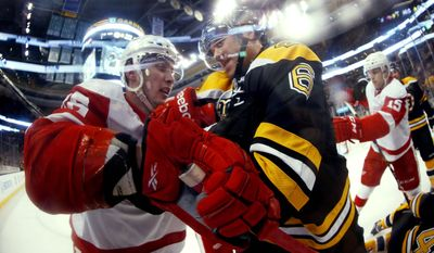 In this photo taken with a fish eye lens, Boston Bruins defenseman Corey Potter (6) struggles with Detroit Red Wings' Riley Sheahan during the first period of a first-round NHL playoff hockey game in Boston on Friday, April 18, 2014. (AP Photo/Winslow Townson)
