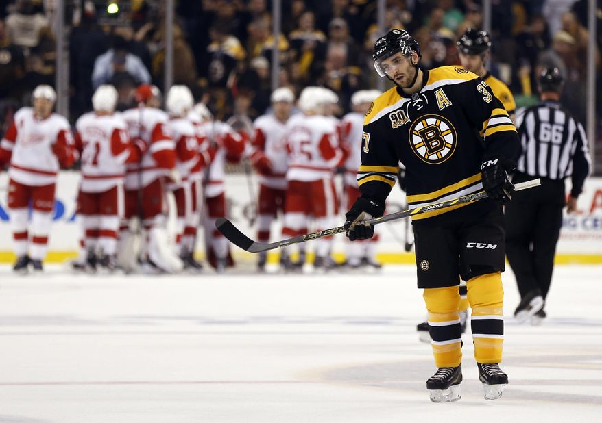 Boston Bruins' Patrice Bergeron skates off the ice as the Detroit Red Wings celebrate their 1-0 win in Game 1 of a first-round NHL playoff hockey series, in Boston on Friday, April 18, 2014. (AP Photo/Winslow Townson)