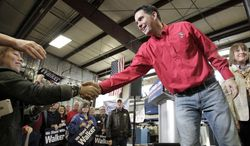 FILE - In this April 15, 2014 file photo Wisconsin Gov. Scott Walker shakes hands with supporters after a campaigning in Dane, Wis. Wisconsin Democrats and their allies who are trying to take out Walker have invested all their hopes in Mary Burke, a Harvard-educated political newcomer whose father started Trek Bicycle when she was a teenager. (AP Photo/Wisconsin State Journal, M.P. King, File)