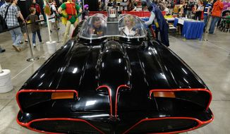 Fans get a chance to sit in the 1966 Batmobile for a picture at the Salt Palace Convention Center in Salt Lake City, Utah,  Friday April 18, 2014, for day two of Salt Lake Comic Con's FanX. (AP Photo/The Salt Lake Tribune, Francisco Kjolseth)