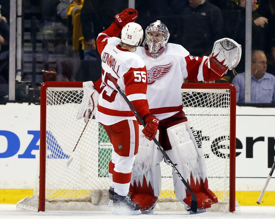 Detroit Red Wings goalie Jimmy Howard celebrates with teammate Niklas Kronwall (55) after the Red Wings defeated the Boston Bruins 1-0 in Game 1 of a first-round NHL playoff series, in Boston on Friday, April 18, 2014. (AP Photo/Winslow Townson)