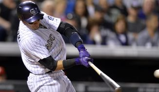 Colorado Rockies' Troy Tulowitzki hits an RBI-single off Philadelphia Phillies relief pitcher Mario Hollands during the sixth inning of a baseball game on Friday, April 18, 2014, in Denver. (AP Photo/Jack Dempsey)