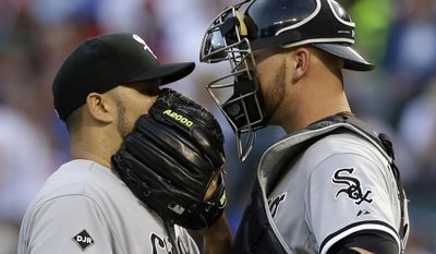 Chicago White Sox's Felipe Paulino talks to catcher Tyler Flowers, right, on the mound after loading the bases against the Texas Rangers in the first inning of a baseball game, Friday, April 18, 2014, in Arlington, Texas. (AP Photo/Tony Gutierrez)