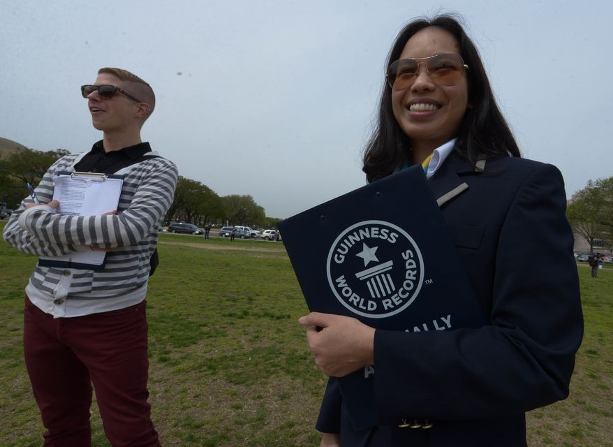 Guinness World Record offical Annie Nguyen, 31, right, and bystander Adam Lammers, 31 look on as participants from Awesome Con D.C. and the Museum of Science Fiction attempt to break a world record for the largest gathering of people dressed as comic book characters at the U.S. Capitol Reflecting Pool on Friday, April 18. The current record holder is China; which stands at 1,530 people, set on April 19, 2011 at the opening ceremony of the International Animation CCJOY LAND. Awesome Con D.C. and the Museum of Science Fiction didn't come close with only 237 people showing up. (Khalid Naji-Allah/ Special to The Washington Times)