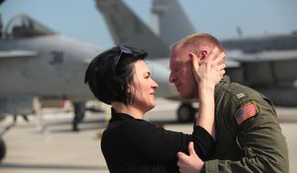 """Christy Brugger greets her husband Lt. Mike Brugger as the """"Ragin' Bulls"""" of VFA-37 return to Oceana Naval Air Station in Virginia Beach, Va., on Thursday, April 17, 2014.  Deployed as part of Harry S. Truman Carrier Strike Group, the squadron participated in Operation Enduring Freedom and several multinational exercises in support of maritime security operations. (AP Photo/The Virginian-Pilot, Steve Earley)  MAGS OUT"""