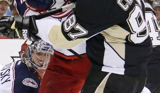 Columbus Blue Jackets' Jack Johnson (7) tries to clear Pittsburgh Penguins' Sidney Crosby (87) from in front of Blue Jackets goalie Sergei Bobrovsky (72) during the second period of a first-round NHL playoff hockey game in Pittsburgh on Wednesday, April 16, 2014.(AP Photo/Gene J. Puskar)