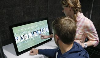 In this April 17, 2014 photo Jamie Gunderson, right, and her husband, John Gunderson, left, visitors from Las Vegas, look at a new interactive touch screen about victims of the bombing that is part of $7 million upgrade at The Oklahoma City National Memorial & Museum, in Oklahoma City. (AP Photo/Sue Ogrocki)