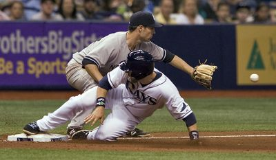 Tampa Bay Rays' Ben Zobrist, bottom, beats the throw to New York Yankees third baseman Scott Sizemore on a single by pinch-hitter Desmond Jennings during the seventh inning of a baseball game Friday, April 18, 2014, in St. Petersburg, Fla. (AP Photo/Steve Nesius)