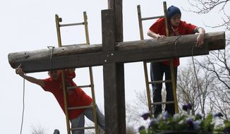 "Volunteers tie the wooden cross that was carried through the streets of Etna, Pa., a Pittsburgh suburb, to the larger cross in the cemetery where their annual ""Drama of The Cross"", service was done on Good Friday, Friday, April 18, 2014. Clergymen from Christian churches in the borough organize a trek with volunteers carrying the wooden cross through borough streets to the cemetery as part of their services for the holiday. (AP Photo/Keith Srakocic)"