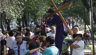 People who were participating in a Holy Week procession stop after a strong earthquake jolted Mexico City, Friday, April 18, 2014. A powerful magnitude-7.2 earthquake shook central and southern Mexico but there were no early reports of major damage or casualties. (AP Photo/Marco Ugarte)