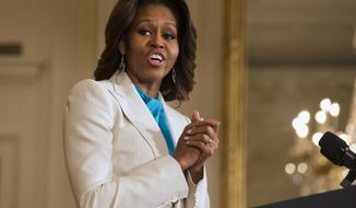FILE - This April 11, 2104 file photo shows first lady Michelle Obama speaking in the East Room of the White House in Washington. When President Barack Obama travels abroad, getting just the leader of the free world doesn't seem to be enough. Countries want the first lady, too. But Michelle Obama won't join her husband when he heads to Asia next week and her absence is likely to sting, especially in Japan. It's the first of four countries on Obama's travel schedule and the only one welcoming him on an official state visit.  (AP Photo/Jacquelyn Martin, File)
