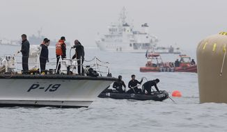 South Korean navy personnel install a buoy to mark the sunken passenger ship Sewol in the water off the southern coast near Jindo, South Korea, Friday, April 18, 2014. Rescuers scrambled to find hundreds of ferry passengers still missing Friday and feared dead, as fresh questions emerged about whether quicker action by the captain of the doomed ship could have saved lives. (AP Photo/Yonhap) KOREA OUT