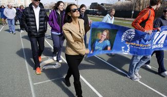 ADVANCE FOR MONDAY, APRIL 21, 2014 - In this Thursday, April 17, 2014, photo, University of Massachusetts nursing professor Adrienne Wald, center, helps carry a banner that features a photo of Krystle Campbell, a UMass nursing student who died in the Boston Marathon bombings in 2013, during a tribute walk on a track at the school in Boston. Wald, who has run the Boston Marathon five time, organized a group of her students last year to work as race volunteers on the sweep team, standing with wheelchair runners they expected to be dehydrated or otherwise needing minor medial care. None of her students was injured in the bombing. (AP Photo/Steven Senne)