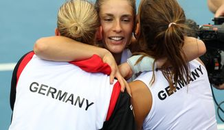 Andrea Petkovic, center, of Germany celebrates with her teammates after winning 6-1, 7-6, in her semifinal match against Samantha Stosur of Australia during the Fed Cup semifinals between Australia and Germany in Brisbane, Australia, Saturday, April 19, 2014. (AP Photo/Tertius Pickard)