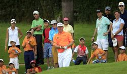 Lee Westwood, center, of England watches his shot on the fifth hole during the third round of the Malaysian Open golf tournament at Kuala Lumpur Golf and Country Club in Kuala Lumpur, Malaysia, Saturday, April 19, 2014. (AP Photo/Lai Seng Sin)
