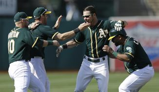 Oakland Athletics' Josh Reddick, second from right, celebrates after making the game-winning hit off Houston Astros' Chad Qualls in the ninth inning of a baseball game Saturday, April 19, 2014, in Oakland, Calif. The A's won 4-3. (AP Photo/Ben Margot)