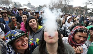 ** FILE ** With the Colorado state capitol building visible in the background, partygoers dance and smoke pot on the first of two days at the annual 4/20 marijuana festival in Denver, Saturday, April 19, 2014. The annual event is the first 420 marijuana celebration since retail marijuana stores began selling in January 2014. (AP Photo/Brennan Linsley)