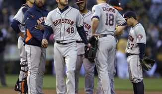 Houston Astros' Jarred Cosart (48) walks off the mound after being removed from the baseball game against the Oakland Athletics by manager Bo Porter, left, in the first inning Friday, April 18, 2014, in Oakland, Calif. (AP Photo/Ben Margot)