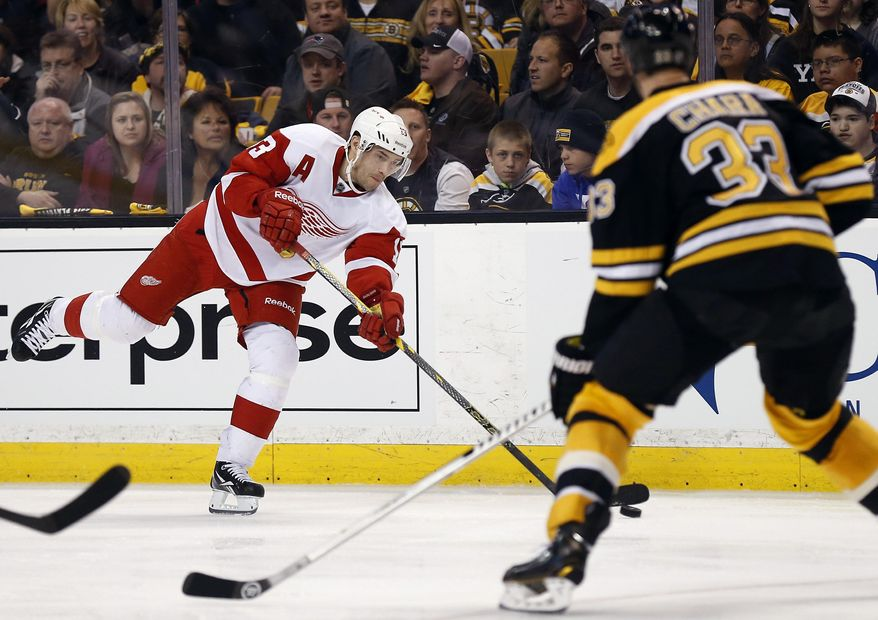 Detroit Red Wings' Pavel Datsyuk lets go a shot as Boston Bruins defenseman Zdeno Chara (33) defends during the third period of Detroit's 1-0 win in Game 1 of a first-round NHL playoff hockey series, in Boston on Friday, April 18, 2014. (AP Photo/Winslow Townson)