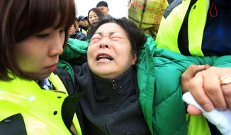 A relative of a passenger aboard the sunken ferry Sewol in the water off the southern coast, weeps as she waits for her missing loved one at a port in Jindo, South Korea, Saturday, April 19, 2014. Rescuers scrambled to find hundreds of ferry passengers still missing Friday and feared dead, as fresh questions emerged about whether quicker action by the captain of the doomed ship could have saved lives. (AP Photo/Ahn Young-joon)