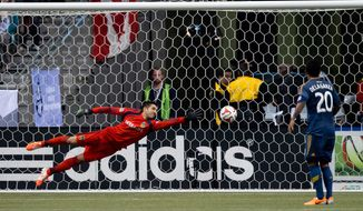Los Angeles Galaxy goalkeeper Jaime Penedo, left, of Panama, allows a goal to Vancouver Whitecaps' Kekuta Manneh (not shown) as Galaxy's A.J. DeLaGarza (20) looks on during the second half of an MLS soccer game on Saturday, April 19, 2014, in Vancouver, British Columbia. (AP Photo/The Canadian Press, Darryl Dyck)