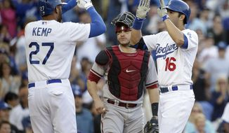 Los Angeles Dodgers' Andre Ethier, right, and Matt Kemp, left, celebrate a three-run home run hit by Ethier in front of Arizona Diamondbacks catcher Miguel Montero during the fourth inning of a baseball game on Saturday, April 19, 2014, in Los Angeles. (AP Photo/Jae C. Hong)