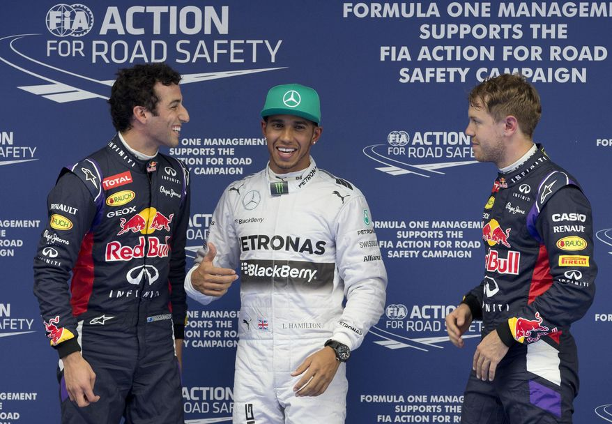 Red Bull Racing driver Daniel Ricciardo of Australia, left, Mercedes driver Lewis Hamilton of Britain, center, and Red Bull Racing driver Sebastian Vettel of Germany, right, chat after the qualifying session of the Chinese Formula One Grand Prix at Shanghai International Circuit in Shanghai, Saturday, April 19, 2014. (AP Photo/Andy Wong)