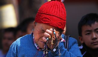 Mother of Nepalese mountaineer Ang Kaji Sherpa, killed in an avalanche on Mount Everest, holds prayers beads in her hand and cries while she waits for his body at Sherpa Monastery in Katmandu, Nepal, Saturday, April 19, 2014. Search teams recovered a 13th body Saturday from the snow and ice covering a dangerous climbing pass on Mount Everest, where an avalanche a day earlier swept over a group of Sherpa guides in the deadliest disaster on the world's highest peak. The Sherpa people are one of the main ethnic groups in Nepal's alpine region, and many make their living as climbing guides on Everest and other Himalayan peaks. (AP Photo/Niranjan Shrestha)