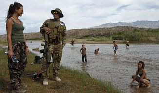 Jennifer Scalzo, left, and her husband Anthony Scalzo stand by the Virgin River during a rally in support of Cliven Bundy near Bunkerville, Nev., Friday, April 18, 2014. (AP Photo/Las Vegas Review-Journal, John Locher)