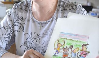 FOR RELEASE SATURDAY, APRIL 19, 2014, AT 12:01 A.M. CDT - In this April 2, 2014 photo, author Jeanne Miller shows off original watercolors created by her son, Justin, as illustrations for the two children's books she has written, at her rural Bancroft, Neb., home. (AP Photo/The Sioux City Journal, Tim Hynds)