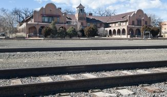 This Thursday, Feb. 13, 2014 photo shows railroad tracks in front of La Castaneda Hotel in Las Vegas, N.M. The building is a historic Fred Harvey House hotel built in 1898 to serve as food-and-rest stop along the Santa Fe Railway. In April 2014, the hotel was purchased by Allan Affeldt, who has also restored another Harvey House hotel in Winslow, Ariz. (AP Photo/Albuquerque Journal, Eddie Moore)